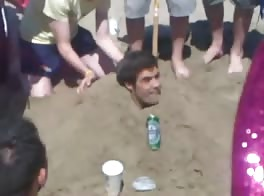 Rugby lads piss hzaing a mate at beach.
